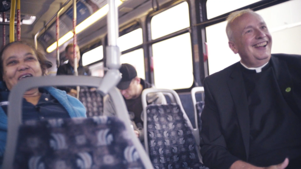 Father Mark smiling on the bus.