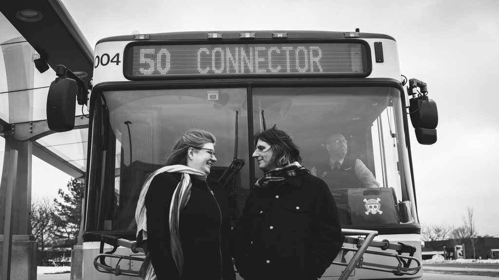 Two people standing in front of a parked bus.
